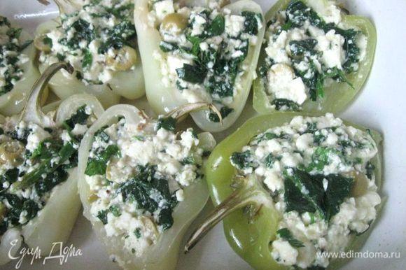 Наполнить начинкой перцы. Температуру в духовке уменьшить до 200°C. Смазать форму оливковым маслом. Отправить перцы в духовку на 12-15 минут.