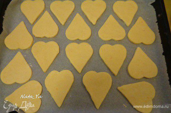 Выложить готовые бисквиты на застеленный бумагой для выпечки противень. Кисточкой смазать верх каждого бисквита яичным белком.