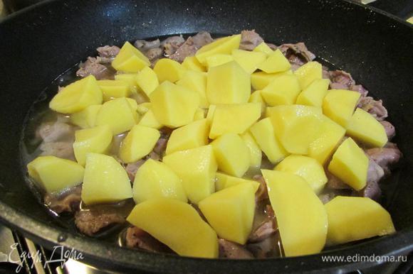 Через 1,5 часа к желудкам добавить картофель. Закрыть сковороду крышкой и тушить до готовности картофеля.