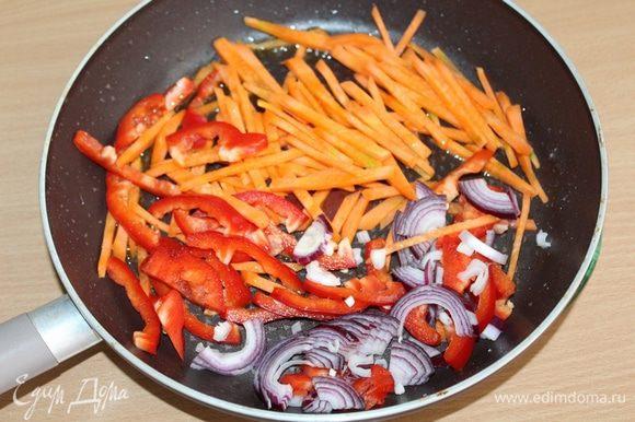 Затем слегка обжарить порезанные соломкой: морковь, перец и лук. Всыпать туда острый перец. Прогреть перец и перемешать с овощами.