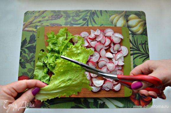 Редис нарежьте также — тонкими полу-дольками, а листья салата с помощью ножниц нарежьте полосками.