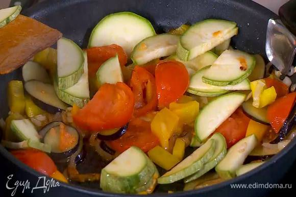 В сковороду с овощами добавить помидор и кабачок, слегка посолить, перемешать и все обжарить.