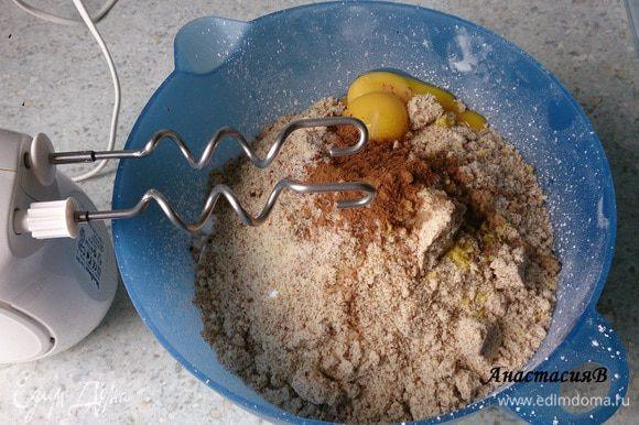 Масло нарезать кусочками. Замесить тесто из миндаля, муки, сахарной пудры, ванильного сахара, 1 ст. л. холодной воды, масла, 2 желтков, цедры лимона, гвоздики и корицы при помощи миксера с насадкой для теста. Тесто замешивать около 5-10 минут, пока оно не станет однородным. Затем поместить немного руками.