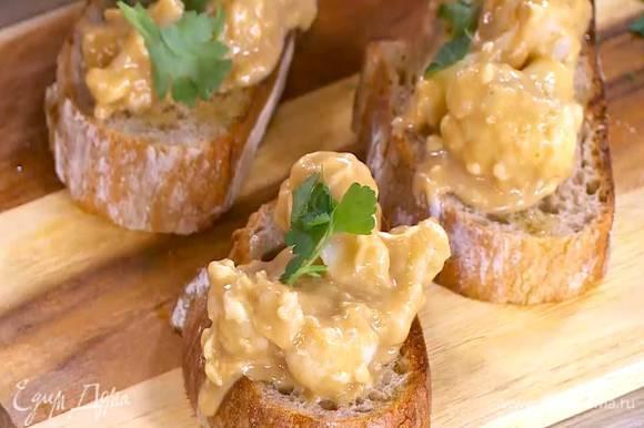 На обжаренный хлеб выложить капусту в соусе и посыпать петрушкой.