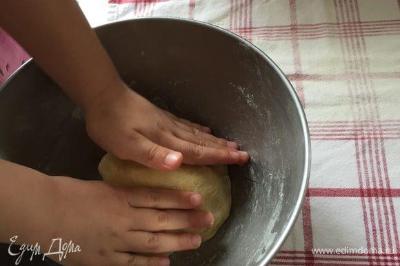 Теперь можно разогревать духовку до 200°С, противень застилаем бумагой. И беремся за самое интересное — вытягивание теста. Кухонное полотенце раскладываем на рабочей поверхности, хорошо присыпаем мукой, в центр выкладываем тесто.
