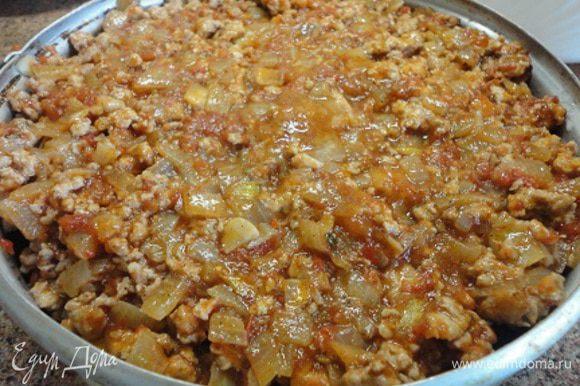 Сверху выложить готовый фарш с соусом. И запекать в духовке при температуре 210°C 15 минут. Затем посыпать оставшимся сыром и еще запекать 10 минут.
