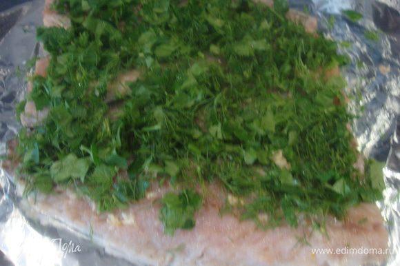 Выдавить чеснок. Зелень мелко порезать (у меня укроп и петрушка), выложить на рыбу.