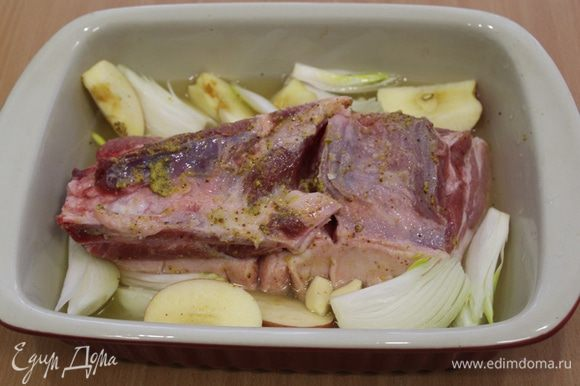 В форму налить воды, примерно около одного стакана и добавить пива. Выложить мясо шкуркой вниз. Разрезать лук и яблоки на 4 части, чеснок почистить. Выложить вокруг мяса.