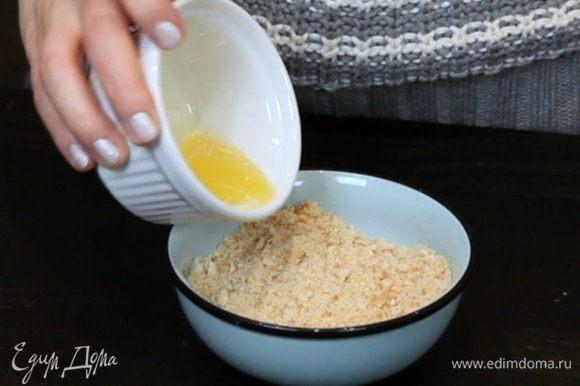 Смолоть печенье в крошку и перемешать с растопленным сливочным маслом.