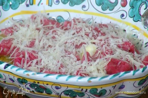 В глубокую тарелку влить оливковое масло, добавить сливочное масло, выложить отваренные ньокки, посыпать оставшимся натертым сыром и подсушенными кедровыми орехами.