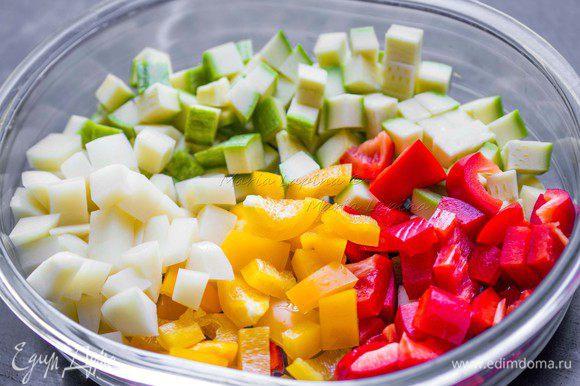 Остальные овощи: картофель, кабачок и перцы нарезаем кубиками чуть меньшего размера, чем баклажан. Баклажан промокнем бумажным полотенцем, снимаем с него влагу, а вместе с ней возможную горечь. Смешиваем все овощи и солим. Овощи нужно немножко не досолить, т. к. в блюде присутствует соленая фета.