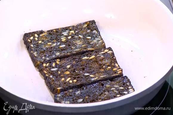 Разогреть в сковороде 1 ст. ложку оливкового масла и обжарить черный хлеб с двух сторон, затем выложить его на бумажное полотенце.
