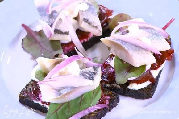 Поджаренный хлеб смазать частью соуса, выложить ломтики свеклы, яичный белок, свекольные листья и кусочки селедки, смазать соусом, сверху разложить замаринованный лук.