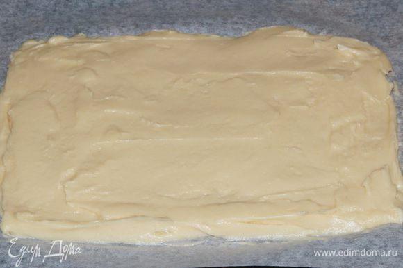 Противень выстилаем пекарской бумагой и равномерно распределяем тесто.