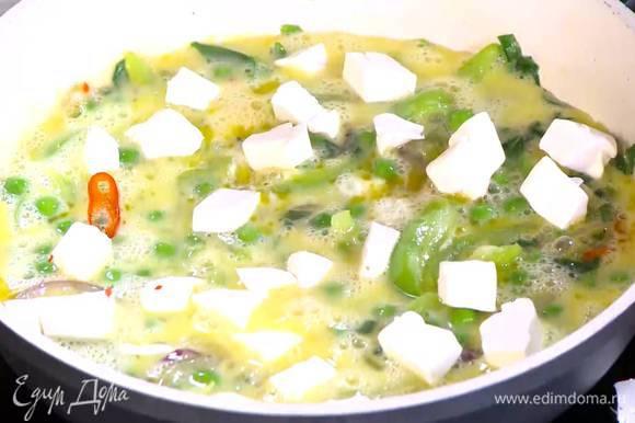 Фету нарезать маленькими кубиками и выложить на яйца с овощами.