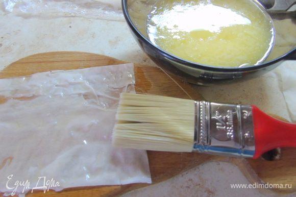 Сливочное масло растапливаем в пиале. Тесто фило нарезаем квадратами и смазываем маслом.