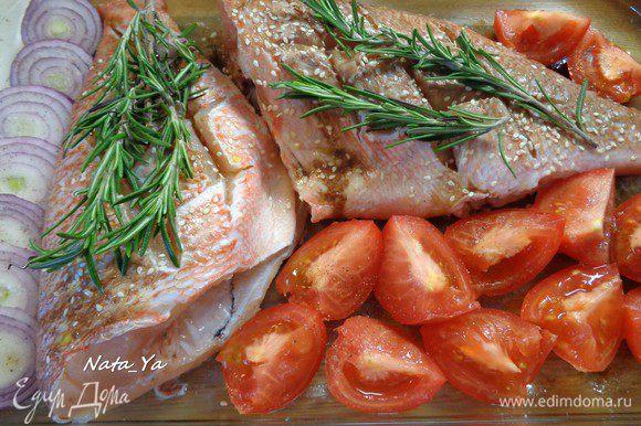 Выложить на каждую рыбку по 2 веточки розмарина. Помидоры разрезать на четвертинки, красный лук — кольцами. Выложить в форму, посолить.