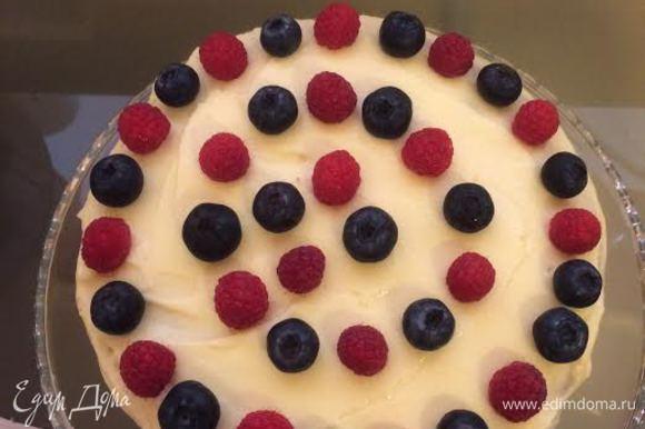 Накрыть второй половиной бисквита. Смазать кремом, украсить малиной и черникой.