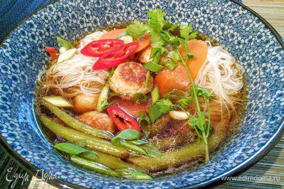 В пиалы разложить леаепшу, разлить суп. Украсить кинзой, зеленым луком и перчиком чили.