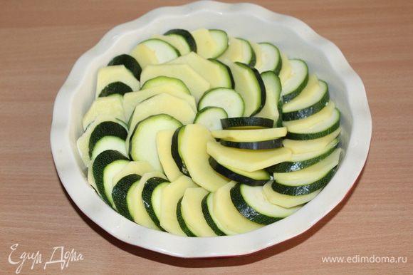 Форму для запекания диаметром 25 см смазать сливочным маслом, выложить туда овощи внахлест в один ряд.