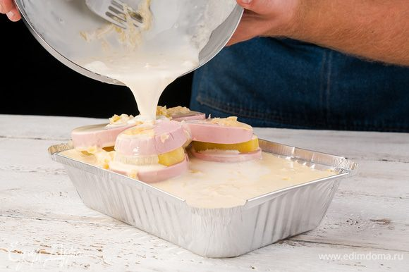 На слой картофеля выкладываем колбасу, нарезанную тонкими кружками, затем лук и чеснок, затем снова картофель и колбасу. Посыпать сверху мелко нарезанной петрушкой и залить запеканку яично-сметанной смесью.