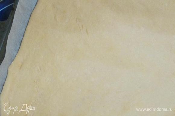 Тесто раскатать, выложить на противень, застеленный пекарской бумагой. Толщина коржа должна быть около 5 мм.