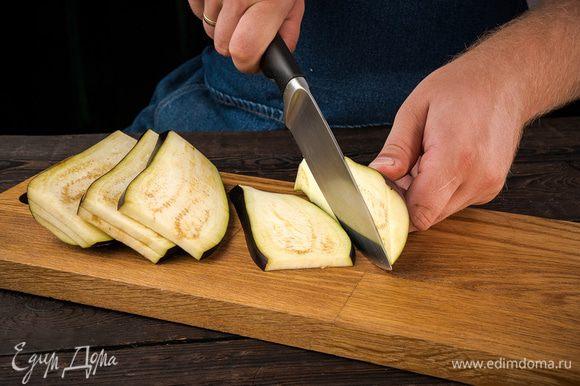 Духовку предварительно разогреть до 200 °С. У баклажанов удалить плодоножки и разрезать каждый вдоль на восемь частей. Уложить в противень срезами вверх, сбрызнуть арахисовым маслом, посолить и поперчить. Отправить в разогретую духовку на 20 минут, затем остудить и нарезать кубиками.