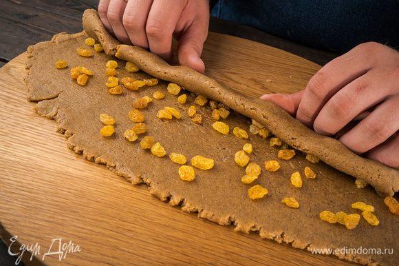 На тесто выложить изюм и сбрызнуть виноградным маслом. Скрутить тесто в рулет.