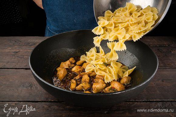 Обжарить в сковороде вок кусочки курицы вместе с маринадом, добавить макароны, все перемешать.