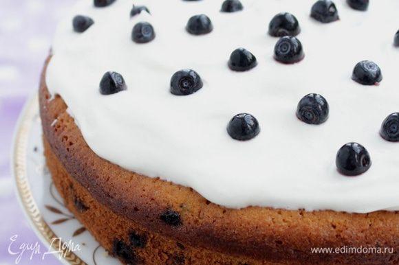 Взбить сахарную пудру с творожным сыром, если получилось слишком густо, можно добавить немного сметаны. Нанести на кекс. Посыпать оставшейся ягодой.