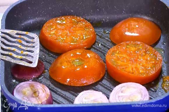 Разогреть в сковороде-гриль 1‒2 ч. ложки оливкового масла и обжаривать лук и помидоры с двух сторон до появления золотистой корочки.