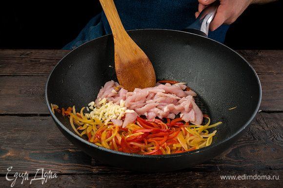 На сковороде обжариваем на растительном масле лук, чеснок и куриное филе, нарезанное на кубики. Добавляем мелко нарезанный болгарский перец, накрываем крышкой на 5 — 7 минут.