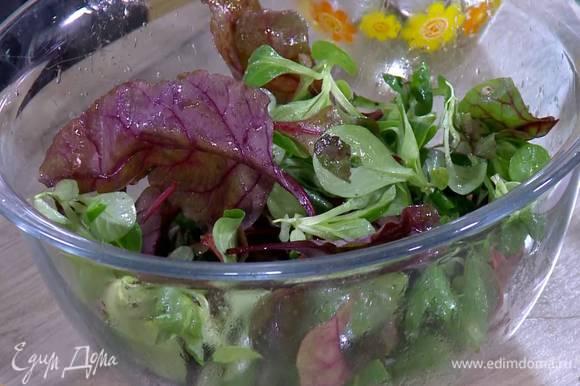 В глубокую посуду влить заправку, выложить салатные листья и все перемешать.