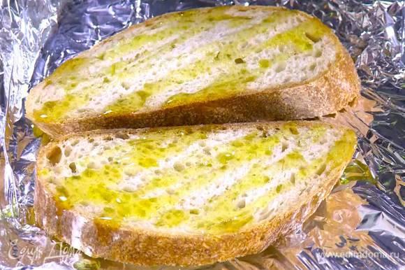 Хлеб выложить на противень, выстеленный пищевой фольгой, сбрызнуть оливковым маслом и поджаривать пару минут под разогретым грилем.