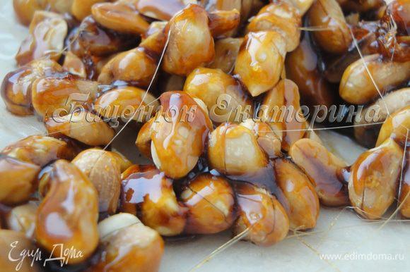 Выкладываем карамелизированный арахис на хорошо промасленную пекарскую бумагу и даем остыть.