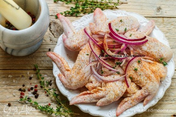 Крылышки хорошо промыть и обсушить. Лук нарезать полукольцами или соломкой, оборвать листики с тимьяна. Соединить крылья, лук, специи, хорошо перемешать и оставить на 2 — 3 часа.