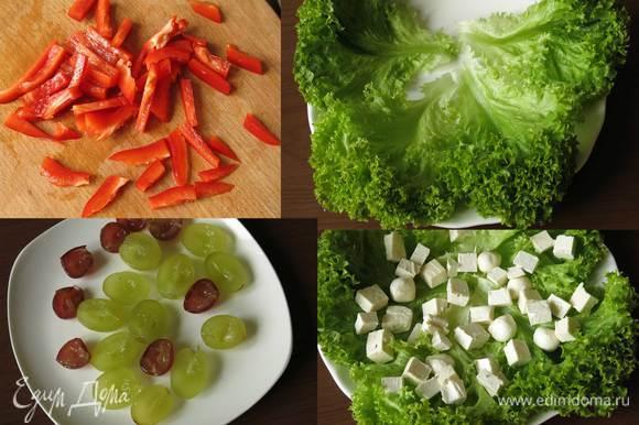 Нарезаем соломкой перец. Выкладываем промытый салат. Разрезаем виноградинки пополам, зубочисткой вынимаем косточки. На салат кладем сыр кубиками и моцареллу.