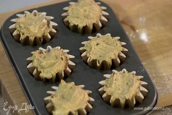 В формы для маффинов поместить бумажные вкладыши и выложить тесто.