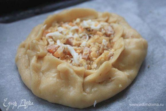 Раскатайте каждую часть теста. В середину выложите начинку и вновь защипните тесто с краев, формируя мешочек. Выложите расстегаи на теплый противень, накройте полотенцем и оставьте на 15 — 20 минут, чтобы они подошли. Потом смажьте их взбитым яйцом и отправьте в духовку на 25 — 35 минут при 180°С. Готовые расстегаи достаньте из духовки, накройте полотенцем и дайте им отдохнуть полчаса. После этого подавайте к столу!