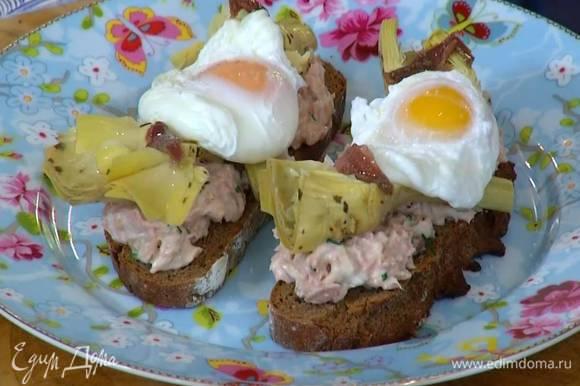 На обжаренный хлеб выложить соус из тунца, сверху поместить артишоки и яйцо пашот, желтки посолить и украсить брускетты оставшимися анчоусами.