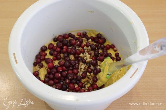 Всыпьте сухую мучную массу в яично-тыквенную смесь и размешайте. Добавьте клюкву и орехи.