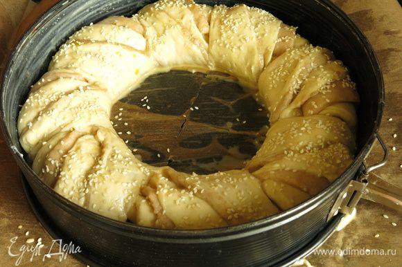 Посыпаем кунжутом, надеваем кольцо. Можно использовать форму большего диаметра, за счет стенок расстойка не поплывет в стороны, будет сформирован высокий хлеб. Выдерживаем в тепле 30 минут, за это время нагреваем духовку до 200°С.