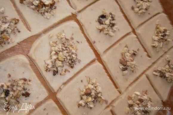 Разрезаем тесто на квадратики примерно 7х7 см и в середину каждого кладем орешки.