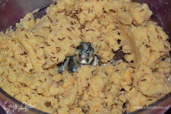 Добавить разрыхлитель, черный перец, травы, сливки и муку. Тщательно перемешать. Добавить тмин и замесить тесто. Солить не нужно, т. к. сыр уже содержит достаточно соли.