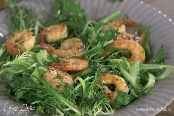 На тарелку выложить салат вместе с соком, посыпать базиликом, сверху разложить креветки.