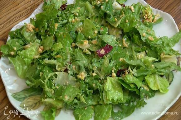 Листья салата смазать заправкой и выложить на блюдо.