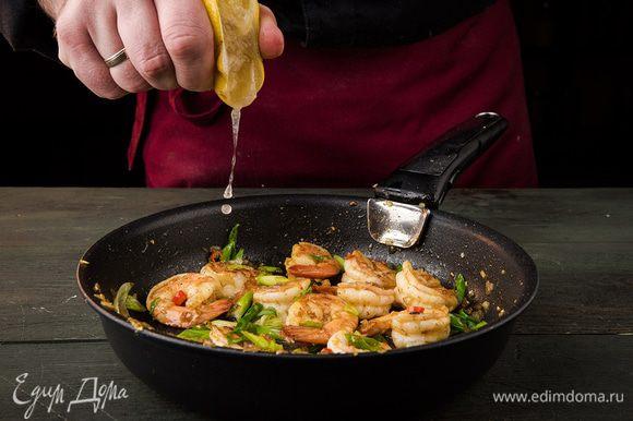 Перец чили, зеленый лук тонко порезать наискосок, добавить к креветкам, посолить и перемешать. Из лимона выжать сок и обжарить все до готовности. Авокадо почистить и, удалив косточку, нарезать тонкими ломтиками, затем сбрызнуть оставшимся лимонным соком.