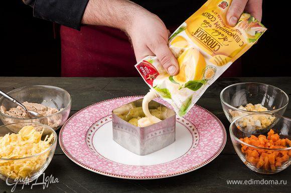 В сервировочное кольцо выложить картофель, смазать майонезом С лимонным соком ТМ «Слобода».