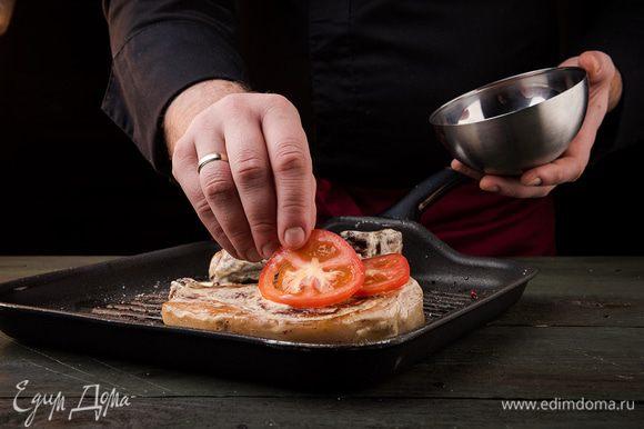 Противень смазать растительным маслом, выложить на него мясо. Помидор нарезать кольцами и положить по колечку на каждый кусочек мяса.