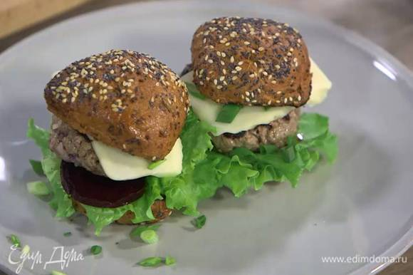 Две обжаренные половинки булочек смазать горчицей, выложить листья салата, замаринованную свеклу, котлеты и сыр, посыпать зеленым луком и накрыть оставшимися половинками булочек.